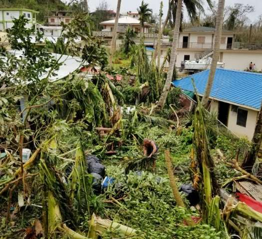 A resident (C) clearing up in Saipan after Super Typhoon Yutu caused widespread destruction across the US Pacific territory isla