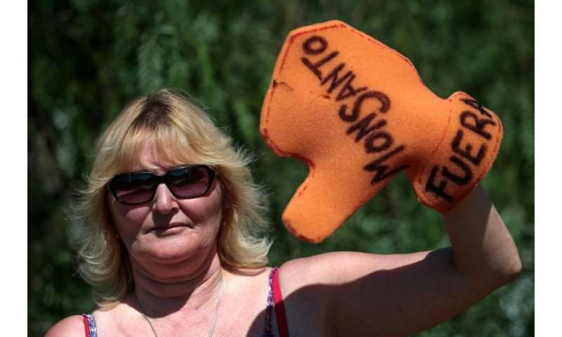 """Argentine environmentalist Sofia Gatica poses with a glove reading """"Monsanto out,"""" as she protests against the use of"""