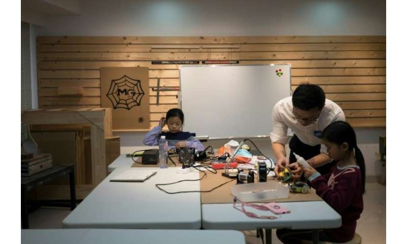 A teacher instructs children at 'MG Space', a small-scale workshop in Shenzhen, southern China