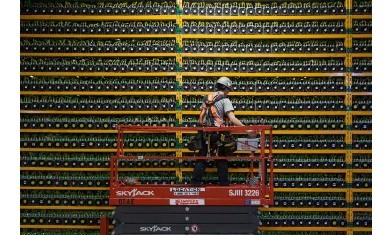 A technician inspects the backside of bitcoin mining at Bitfarms in Saint Hyacinthe, Quebec