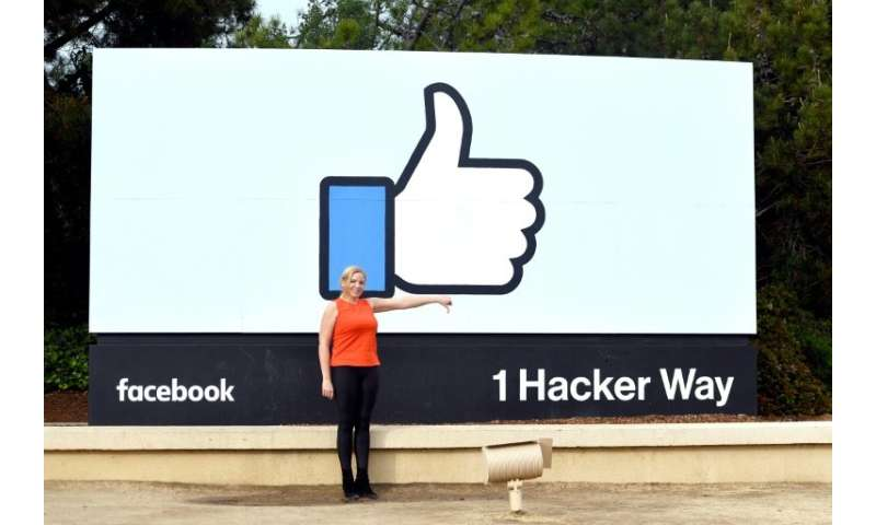 A woman makes a thumbs down sign in front of Facebook's corporate headquarters in Menlo Park, California. The world's biggest so