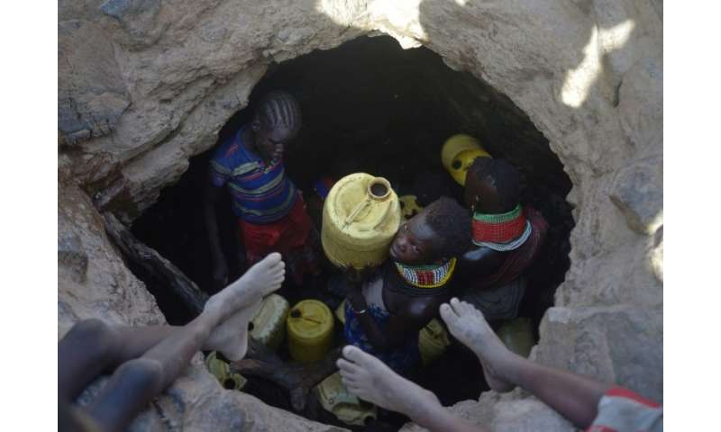 A young girl passes up a jerrycan filled with murky water from underground rocks in northern Kenya's Turkana county. A crippling