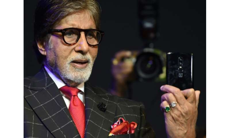 Bollywood actor Amitabh Bachchan holds a mobile phone during a commercial event in Mumbai