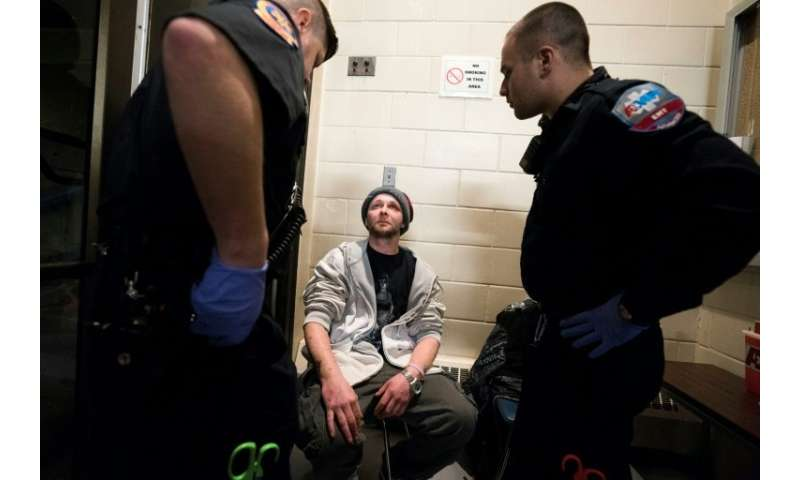 Cody, 31, who fell back into addiction in February, is checked by paramedics as he enters the Safe Station program at the Centra