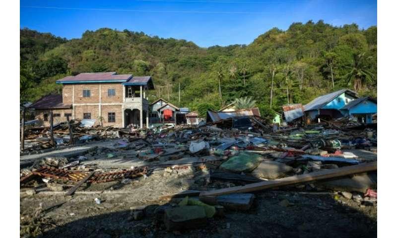 Damaged buildings are seen amid debris along a coastal area in Palu