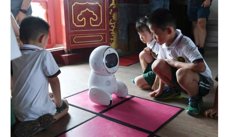 Each time the children get an answer right, the robot reacts with delight, its face flashing heart-shaped eyes