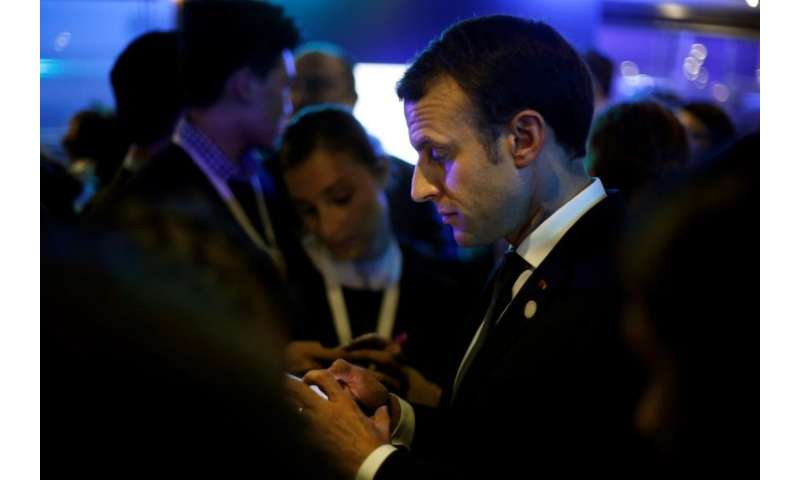 Even French President Emmanuel Macron checks his 'mobile multifonction'.