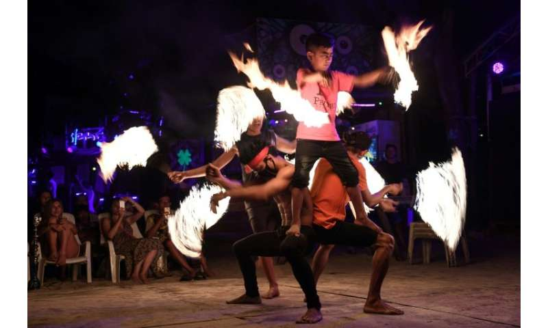 Fire dancers perform for tourists on the southern Thai island of Koh Phi Phi, which is swamped by up to 4,000 daily visitors