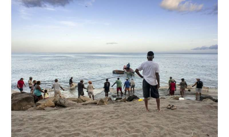 Fishermen and tourists gather on a beach near the town of Le Carbet of the French Caribbean island of Martinique in July, 2014