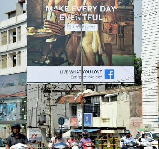 Indian commuters pass a poster advertising Facebook's 'Live What You Love' campaignaction for any attempt to influence polls by