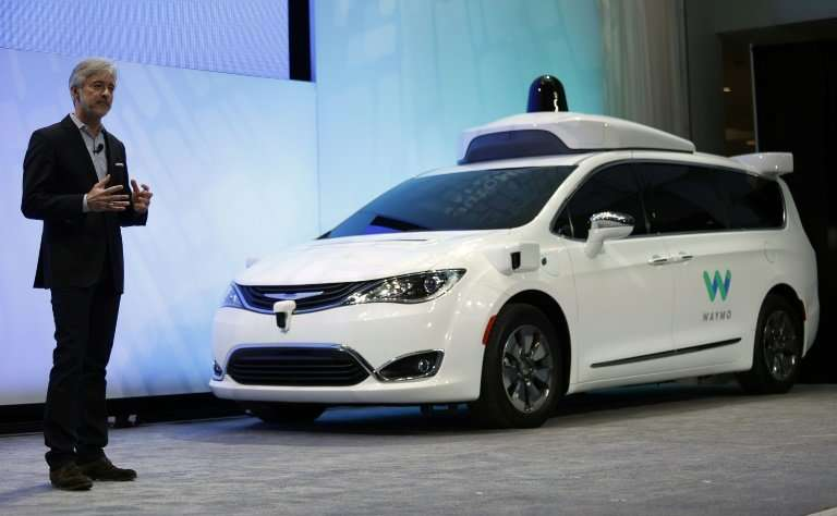 John Krafcik, CEO of Waymo, is seen at the 2017 North American International Auto Show with a customized Chrysler Pacifica Hybri