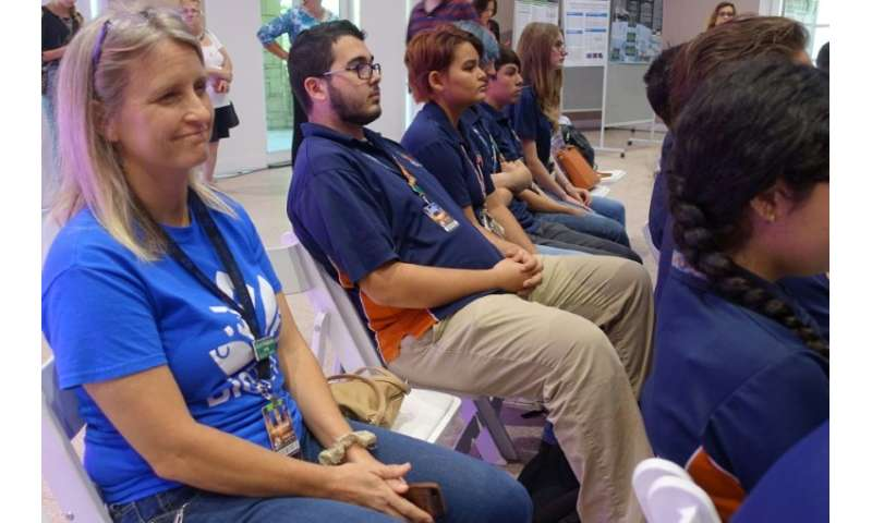 JoLynne Woodmansee (L), a teacher at BioTECH High School, sits with her students during at an event at Fairchild Tropical Botani