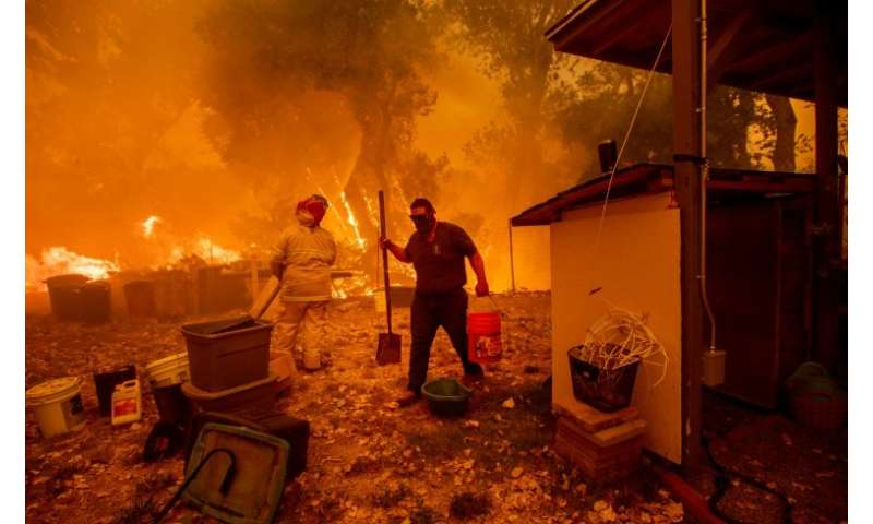 Lane Lawder tries to save his home near Clearlake Oaks, California, on August 4, 2018