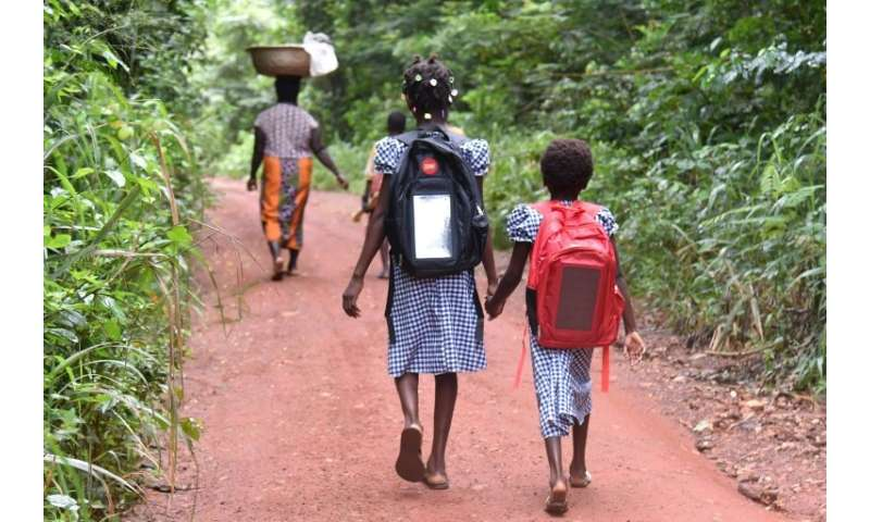 Last year, 13-year-old Lucienne, shown here walking to school with Marie-France, could not go to school at all because their mot