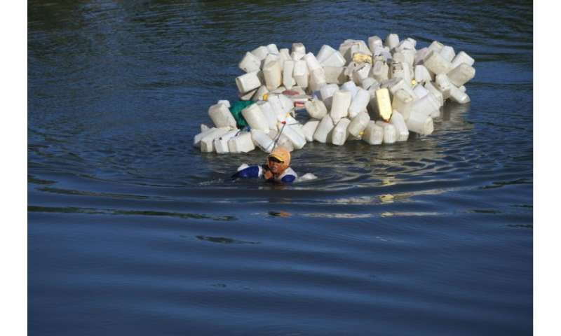Mama Hasria swims with hundreds of jerry cans to collect clean drinking water for her village