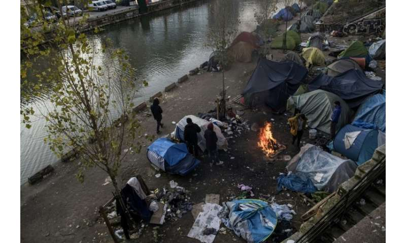 Migrants living in on the streets of Paris struggle to keep themselves warm as temperatures drop below freezing