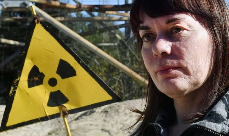 Natalia Shevchuk stands by a radioactive sign in the ghost town of Pripyat, as she revisits her abandoned childhood home
