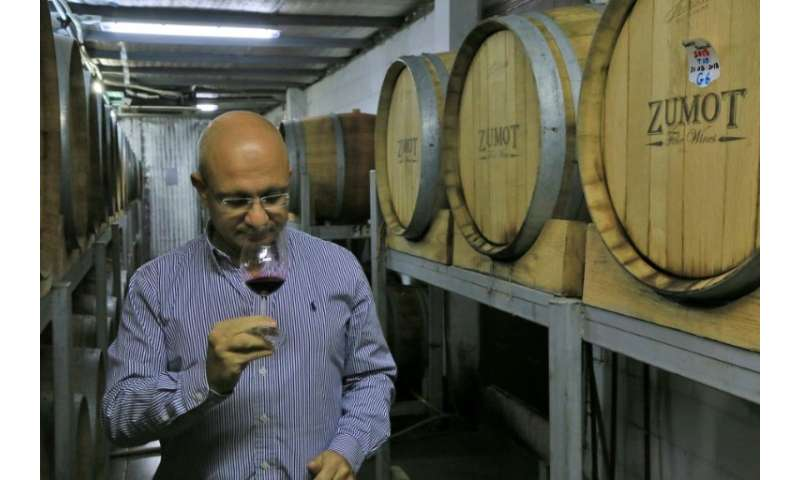 Omar Zumot, manager of Amman's Saint George winery and who studied winemaking in France, samples a glass as two Jordanian famili