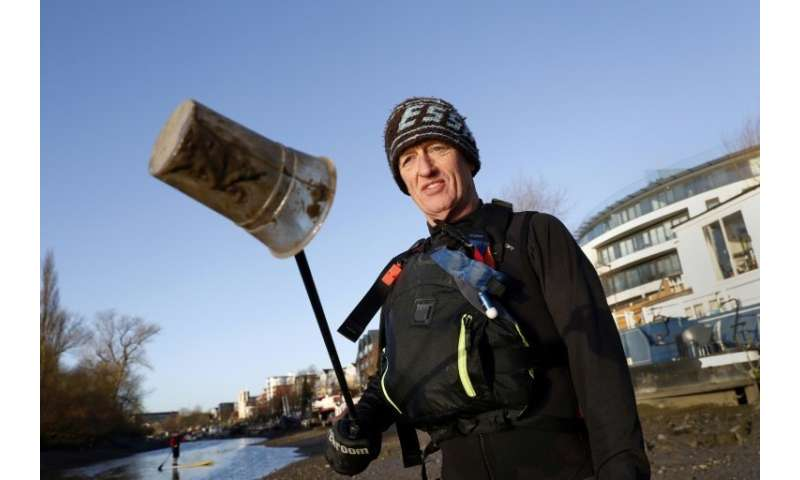 Paul Hyman holds up a plastic cup collected from the Thames