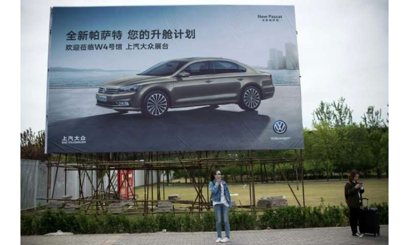 People stand under a billboard advertising a Volkswagen car on the eve of the Beijing Auto Show in Beijing