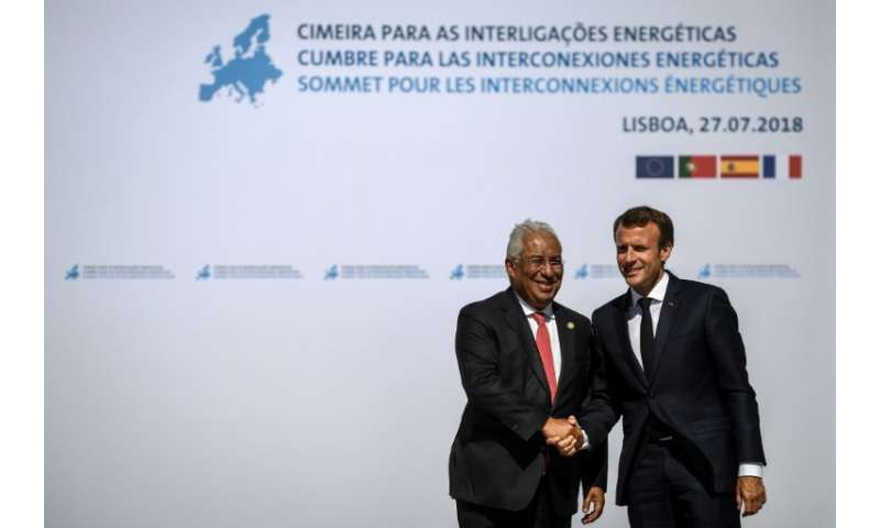 Portuguese Prime Minister Antonio Costa (L) greets French President Emmanuel Macron as he arrives for the Energy Interconnection