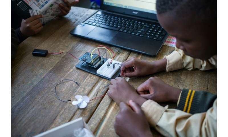 Pupils at the coding club in Ivory Park take wires from the breadboard—the base for building an electronics circuit—to a fan tha