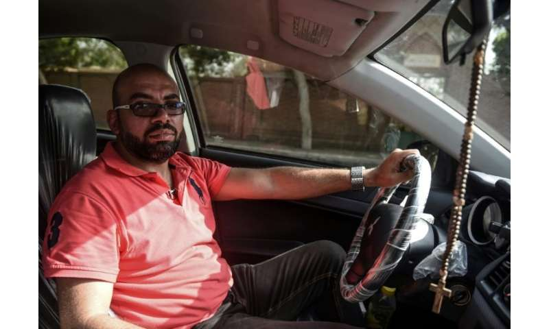 Ramez Wagih, an accountant in the morning and Uber driver in the afternoon, in his car in Cairo