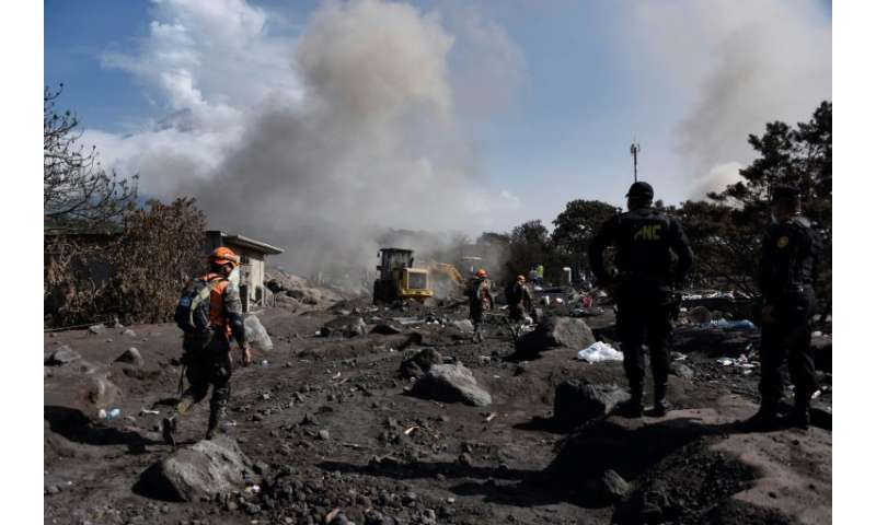 Rescue workers rush to save any survivors in the shadow of Guatemala's Fuego volcano, in San Miguel Los Lotes