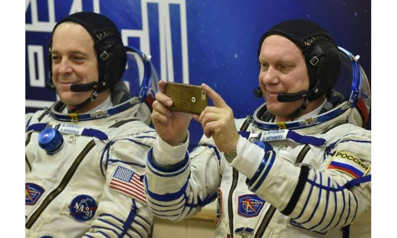 Roscosmos cosmonaut Oleg Artemyev takes a last-minute snap, alongside NASA astronaut Richard Arnold, before they headed into spa