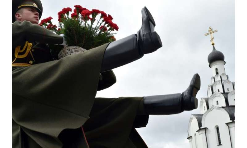 Soldiers bearing flowers at the Chernobyl victims' memorial in Minsk