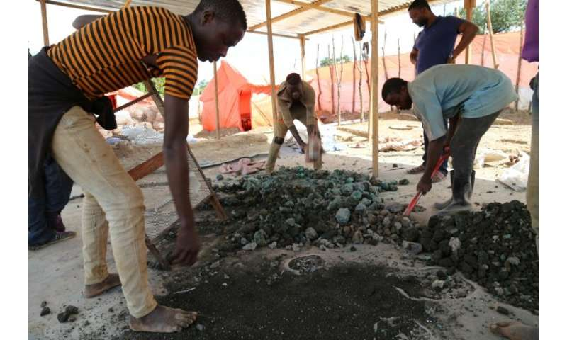 Subsistence miners on the road between Kolwezi and Lubumbashi sift chunks of cobalt from soil