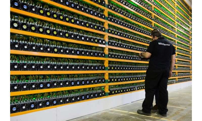 Technicians inspect bitcoin mining at Bitfarms in Saint Hyacinthe, Quebec, as the world's most popular cryptocurrency marks its