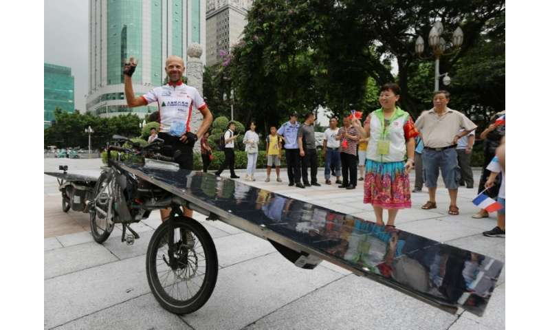 The bike is equipped with two solar panels—one in the front and another on a trailer behind