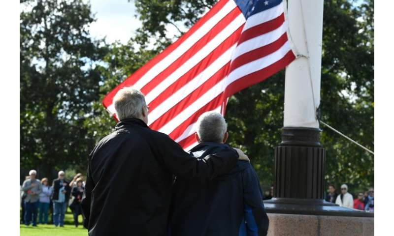 The half-brothers look on as the US flag is raised in the grounds of the Normandy American Cemetery and Memorial at Colleville-s