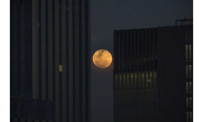 The moon rises between two office buildings in Bangkok on January 31, 2018
