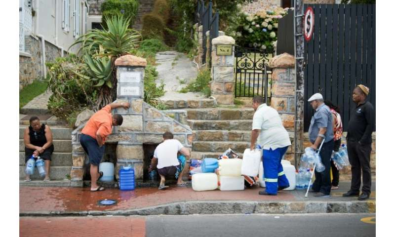 The new normal? People in the Cape Town suburb of St. James queue to collect drinking water from pipes fed by an underground spr