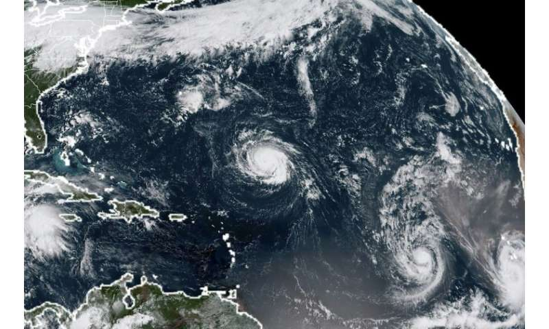 This US satellite image taken on September 9, 2018, shows (L-R) hurricanes Florence, Isaac and Helene in the Atantic Ocean