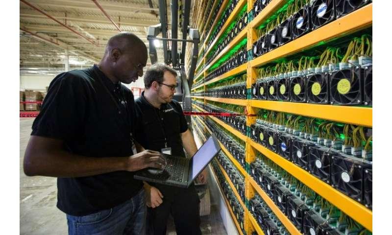 Two technicians look at bitcoin mining at Bitfarms in Saint Hyacinthe, Quebec