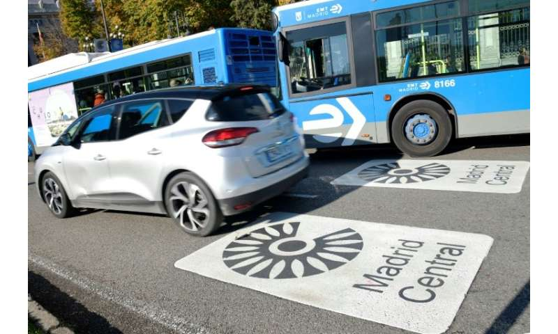 """Vehicles ride over signs saying """"Madrid Central"""", where the city has launched tough new traffic restrictions in a bid"""