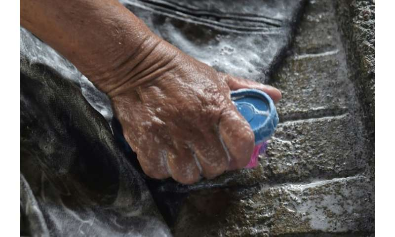 Washerwomen rub dirty clothes against rough stones at an old public laundry in Quito