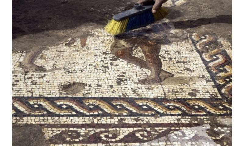 Workers from the Israeli Antiquity Authority clean a rare Roman-era mosaic on February 8, 2018 north of Tel Aviv which archaeolo