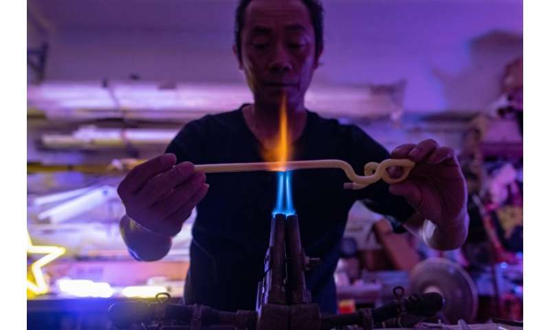 Wu Chi-kai bends glass tubes dusted inside with fluorescent powder into shape over a powerful gas burner