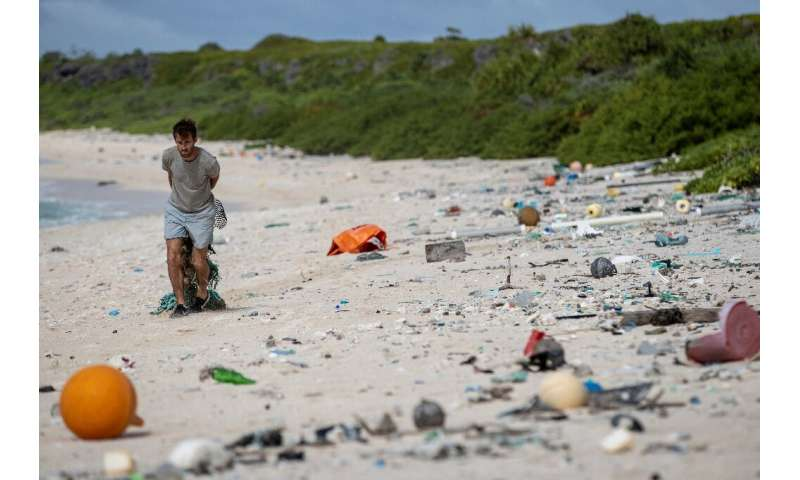 A beach clean-up team member collecting rubbish on Henderson Island