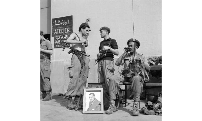 A file photo from November 1, 1956 shows Egyptian soldiers with a portrait of then president Gamal Abdel Nasser in Port Said at