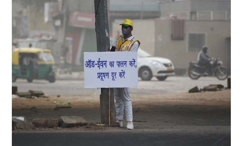 A volunteer in smog-choked New Delhi displays a placard warning drivers of the new odd-even number plate system in effect that s