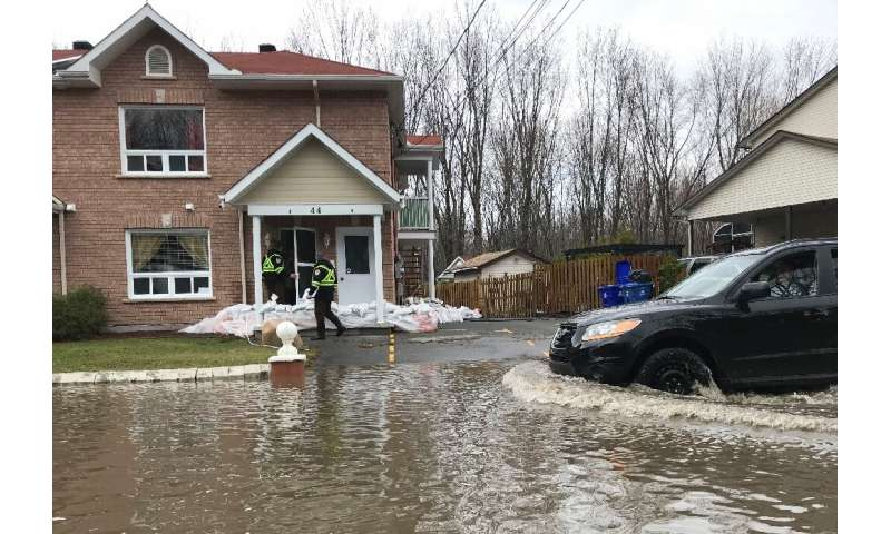 Firefighters check on people in their homes in preparation for increased flooding in Gatineau, Quebec