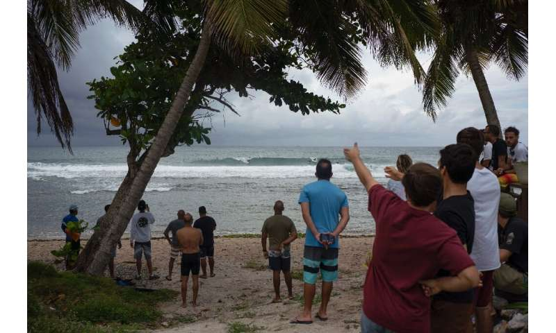 People gather at the coast hours before the Tropical Storm Dorian enters in Patillas, Puerto Rico on, August 28, 2019