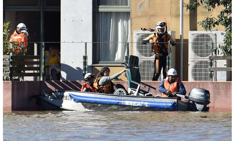 Rescuers moved people by boat from a retirement home that was flooded after Typhoon Hagibis hit Japan