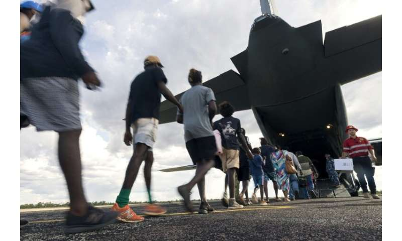 Residents of McArthur River, a remote town in the Northern Territory, boarding an Australian military plane as authorities evacu