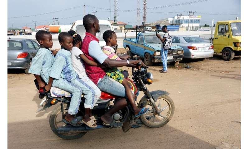 Room for one more? A traditional motorcycle taxi on Lagos roads—overladen and not a crash helmet in sight